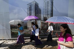 People walk by a construction site of new apartment buildings in Yangon